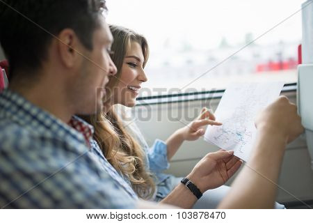 Young couple with a map in the train