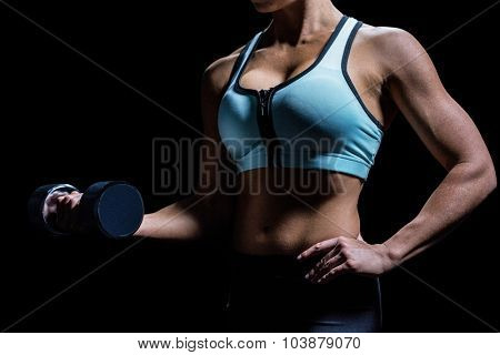 Midsection of woman lifting dumbbell against black background