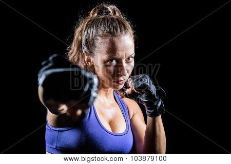 Portrait of female fighter punching against black background