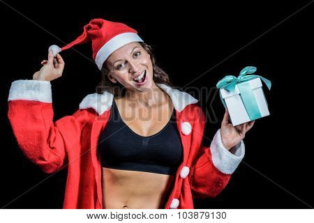 Portrait of female athlete in Christmas costume and holding gift against black background