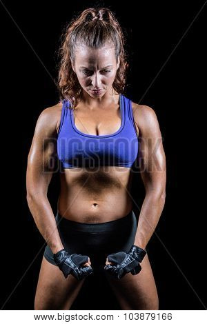 Female fighter flexing muscles against blackground