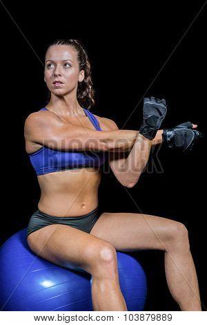 Athlete working out on exercise ball against black background