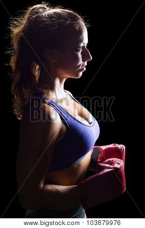 Side view of thoughtful boxer with gloves against black backgroundq
