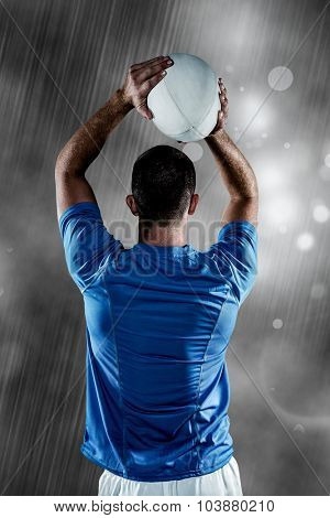 Rear view of rugby player throwing ball against rain