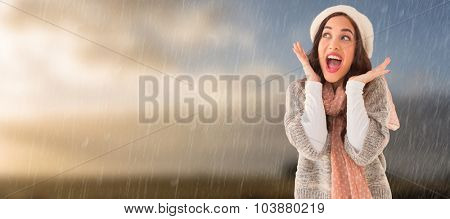 Portrait of a astonished brunette against cloudy sky