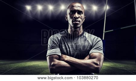 Portrait of confident rugby player with arms crossed against rugby stadium