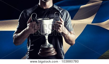 Victorious rugby player holding trophy against rugby stadium