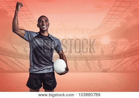 Happy sportsman with clenched fist holding rugby ball against orange