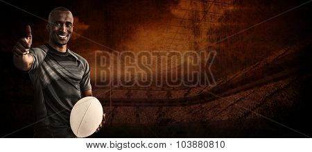 Portrait of confident rugby player smiling and showing thumbs up against rugby stadium