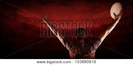 Rear view of rugby player holding ball with arms raised against rugby stadium