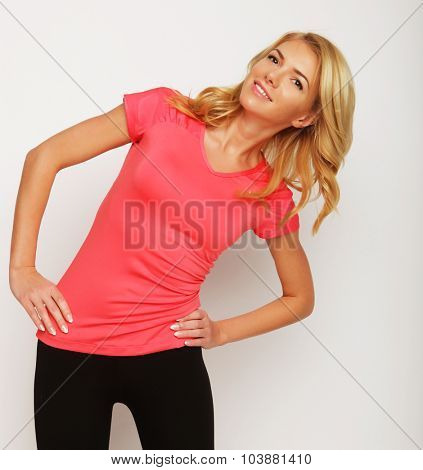 Beautiful young fitness trainer standing isolated over white background