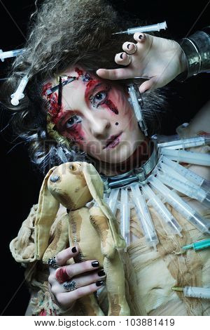 Young woman with creative make up holding little rabbit. Halloween theme.
