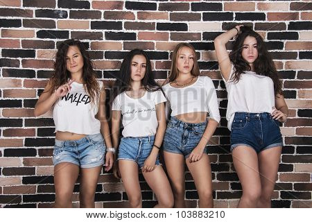 Four Young Girls In White T-shirts And Jeans Shorts Standing Near Brick Wall Looking At The Camera