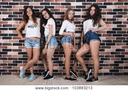 Four Young Girls In White T-shirts And Jeans Shorts Standing Near Brick Wall