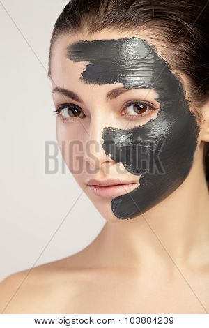 Young woman in mask for face of the black clay