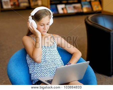 A teenage girl with headphones sitting in a library