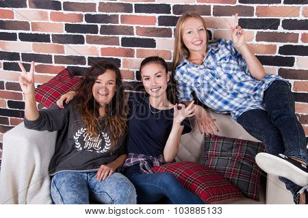Three Young Beautiful Girlfriends Smiling Sitting On The Couch