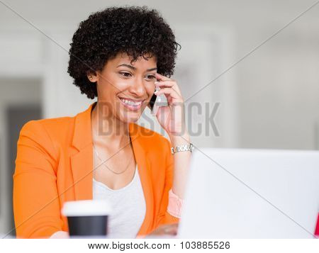 Portrait of young businesswoman in office holding her mobile