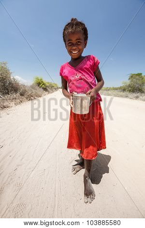 MORONDAVA, MADAGASCAR - DECEMBER 08 Portrait of unidentified smiling girl with can, December 08, 2013, Morondava region, Madagascar. Children in Madagascar are friendly and often barefoot.