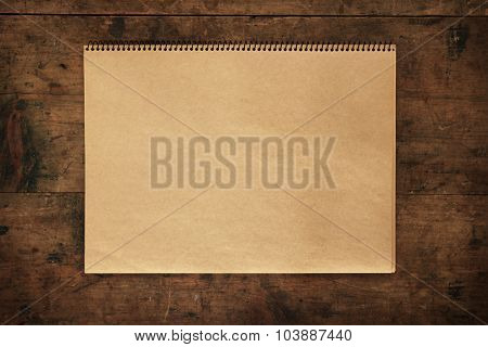 Blank brown paper scrap book on rustic retro table or wall.