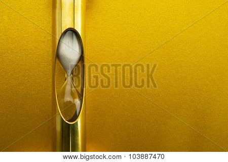 Golden time, gold hour glass in front of gold wall.