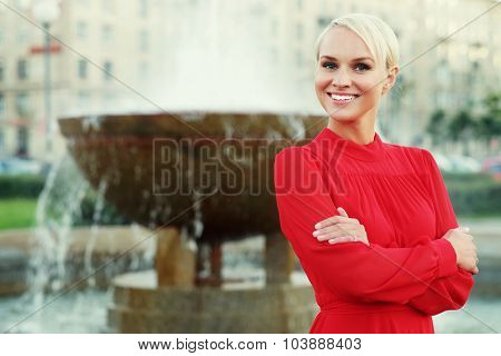 Fashionable young blond woman wearing red dress, summer day