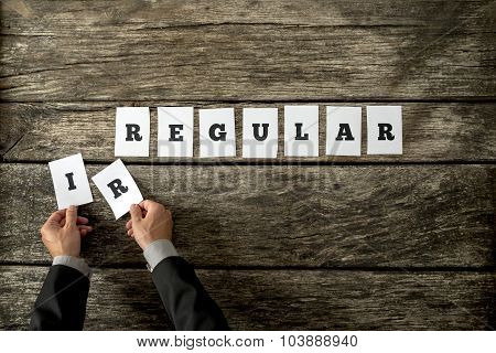 Top View Of Man In Elegant Suit Removing Letters Ir From The Word Irregular