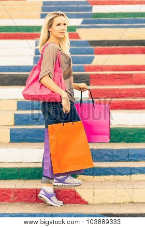 Young Slim Blonde Woman Holding Shopping Bags Stands On The Stairs