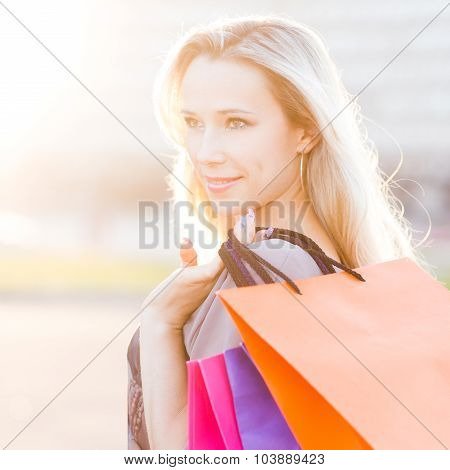 Young Woman Stands With Shopping Bags Against Sun