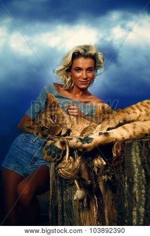 blonde woman playing with lion cub on background with beautiful blue sky and storm clouds.