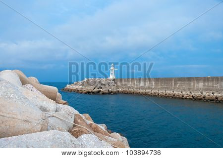 Lighthouse In Harbor With Blue Sky On Background