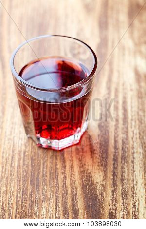 Single glass with red drink over wood table