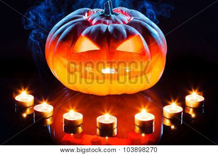 Halloween pumpkin with scary face and burning candle