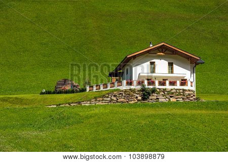 Traditional Alpine House On Green Meadow