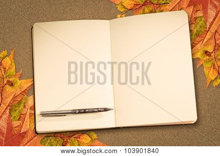 Notebook and pen against autumn leaves pattern