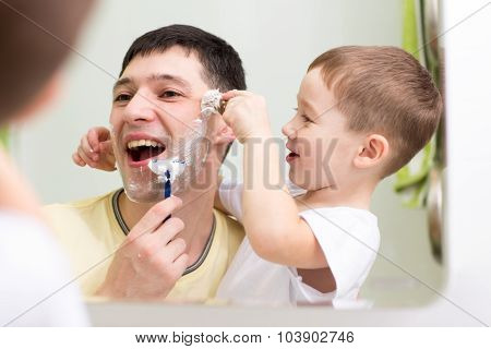 child boy and his father shave looking at mirror in bathroom