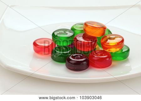 glass colored candies on a white plate