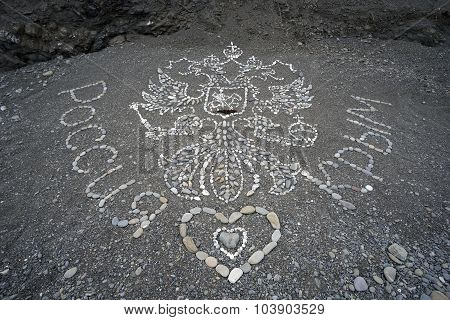 The Coat Of Arms And  Inscription Russia - Crimea Lined With Sea Pebbles On The Beach .