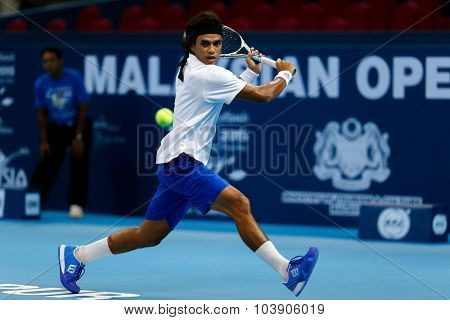 KUALA LUMPUR, MALAYSIA - SEPTEMBER 26, 2015: Syed Mohd Agil of Malaysia plays a backhand shot in his qualifying match in the Malaysian Open 2015 Tennis tournament held at the Putra Stadium, Malaysia.
