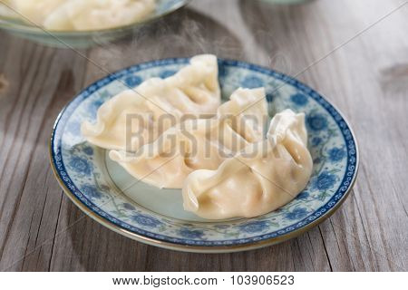 Fresh dumpling on plate. Chinese cuisine with hot steams on vintage wooden background. Fractal on the plate is generic print.