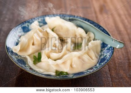Fresh dumplings soup on plate with hot steams. Chinese dish on rustic old wooden background.