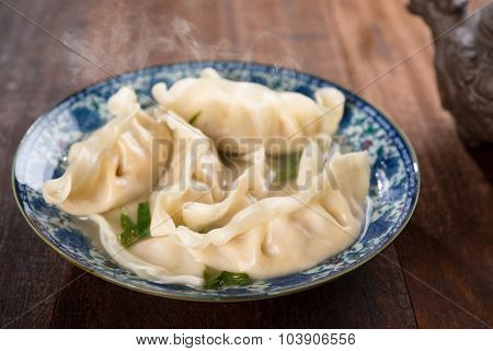 Fresh dumplings soup on plate with hot steams. Chinese food on rustic old wooden background.