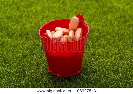 Red bucket full of orange pills standing on the grass