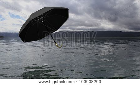 Umbrella floating above water, with distant mountains and cloudy sky on background.