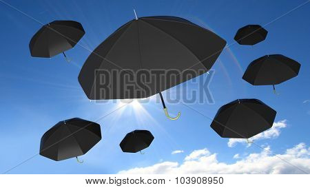 Classic black open umbrellas on blue sky with sun and some clouds background.
