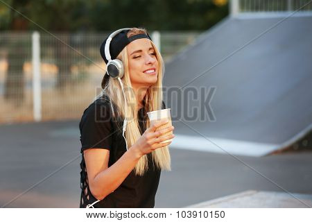 Young woman with earphones outside