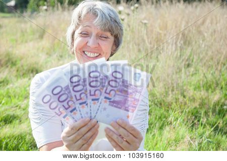 Old age woman holding a lot of money