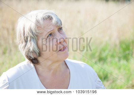 Old age woman looking up while being outside