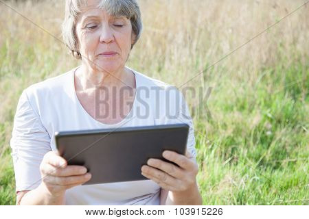 Old age woman using tablet device