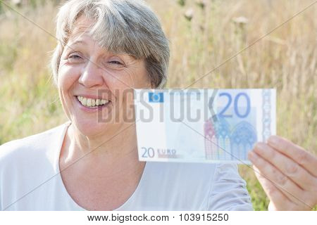 Senior woman holding twenty euro note